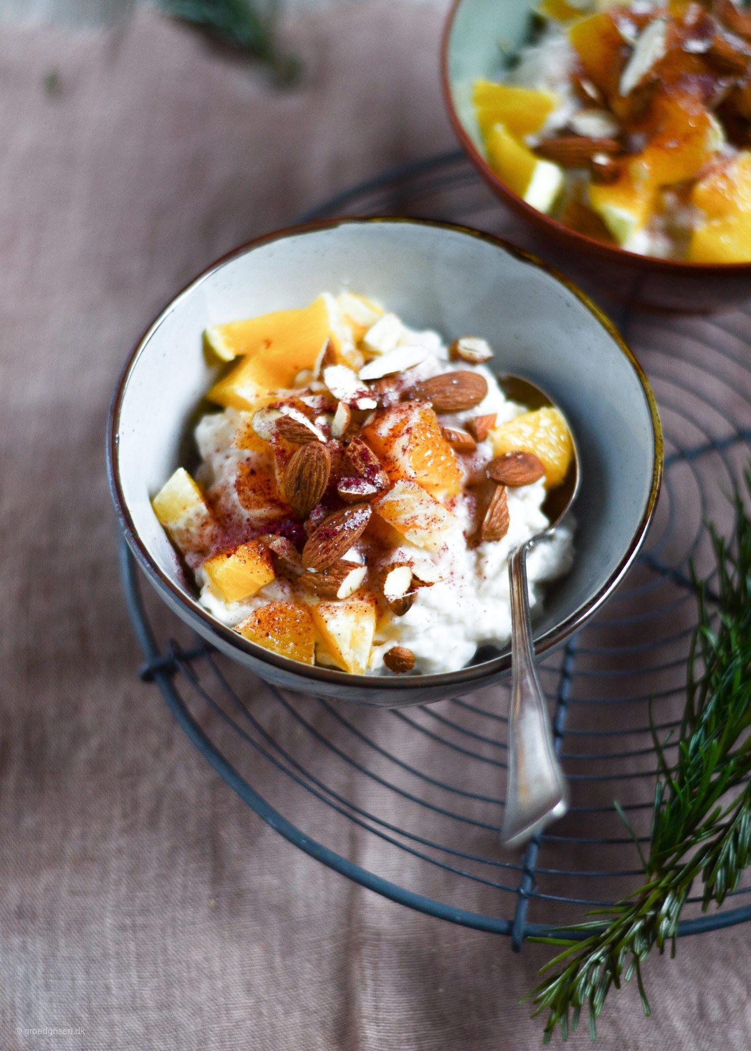 vegansk risengrød med mandelmælk, appelsiner, mandler og tranebærsukker